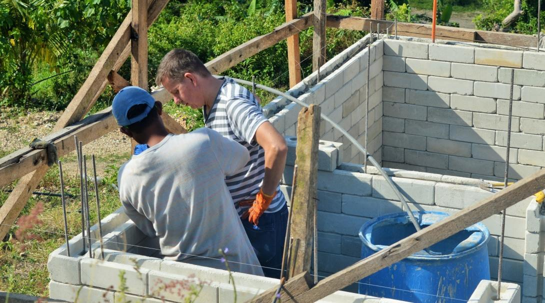 Projects Abroad volunteer is pictured with a local building helping to rebuild homes and schools as part of a disaster relief project during his building volunteer work in the Phillippines.